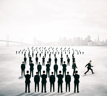 business change: Different deirection concept with arrow shaped crowd of businesspeople going in one direction and just one person walking away