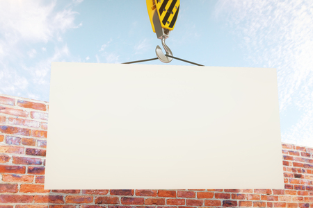 billboard background: Blank board on crane hook with clear sky and brick wall in the background. Mock up, 3D Rendering