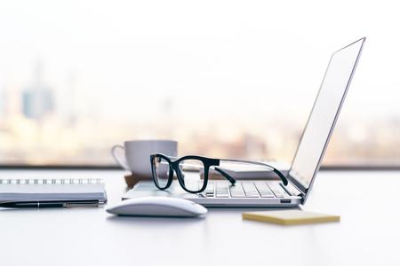 Lateral de escritorio de oficina con ordenador portátil, vasos y otros artículos Foto de archivo - 55888633