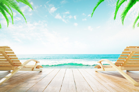 chaise longue: Two chaise longues at the beach with clear skies and palm trees Stock Photo