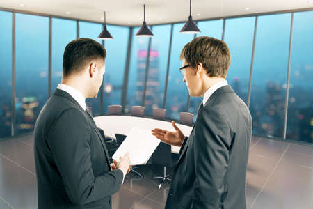 two piece: Two businessmen holding piece of paper and discussing something in conference room interior at night. 3D Rendering Stock Photo