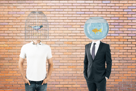 fishtank: Businessperson and casually dressed man with fishtank and birdcage instead of heads on brick background