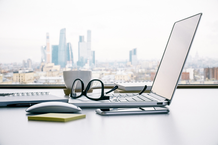Sideview of office table with laptop, glasses and other items on Moscow city background