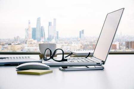 Sideview van bureaulijst met laptop, glazen en andere punten op de stadsachtergrond van Moskou