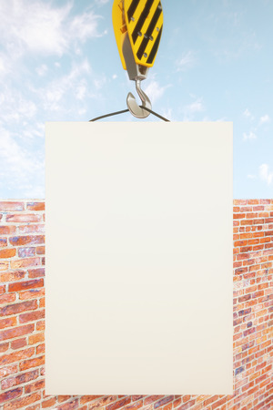 hook up: Blank poster on crane hook with clear sky and brick wall in the background. Mock up, 3D Rendering