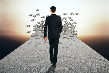 misty: Vagueness concept with businessman walking on road that is breaking into puzzle pieces. Misty landscape background. 3D Rendering Stock Photo