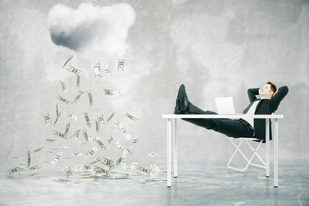 raining: concepto de crecimiento financiero con el empresario sentado en la mesa con los pies en alto y mirando a la lluvia de dinero resumen en cuarto de concreto. Representación 3D