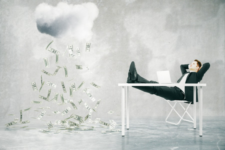 raining: Financial growth concept with businessman sitting at table with feet up and looking at abstract money rain in concrete room. 3D Rendering Stock Photo