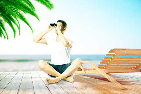 Man Looking Into Binoculars Next To Chaise Longue At The Beach Stock on chaise recliner chair, chaise furniture, chaise sofa sleeper,