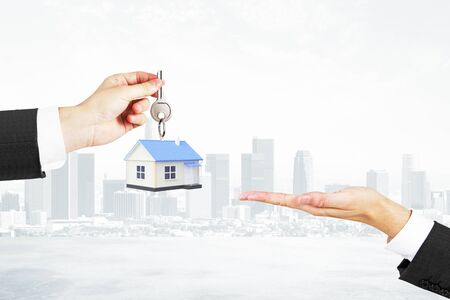 sold small: Mortgage concept with businessman handing house with key to another man on foggy city background