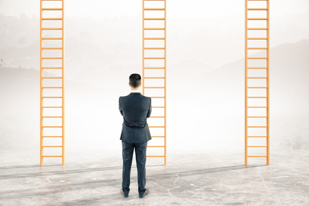 carreer: Thoughtful businessman looking at career ladders on abstract landscape background Stock Photo