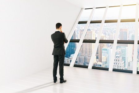pondering: Thinking businessperson in white interior with panoramic windows and city view. 3D Rendering Stock Photo