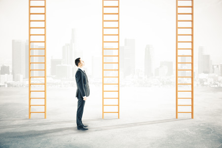 carreer: Businessman looking at career ladders on blurry city background Stock Photo