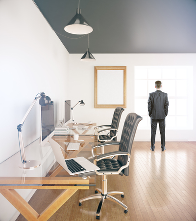 sideview: Businessman looking outside of window in office with two workplaces and blank picture frame. Sideview. Mock up, 3D Rendering