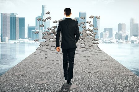 coming together: Success concept with businessman walking on road that is being assembled from puzzle pieces on city background. 3D Rendering Stock Photo