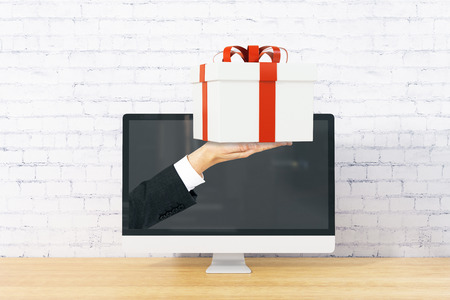handing: Computer monitor with businessman handing present on wooden desktop and brick background. Online shopping concept. 3D Rendering Stock Photo
