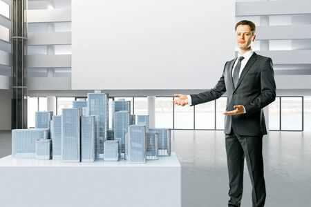 estate planning: Businessman in interior standing next to city model with billboard in the background. Mock up, 3D Rendering Stock Photo