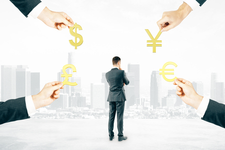 four hands: Thinking businessman and four hands holding pound, dollar, euro and yuan signs on abstract city background Stock Photo