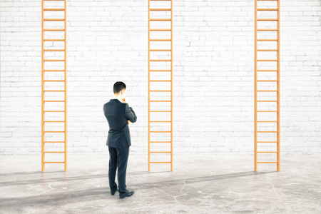carreer: Brick interior with thoughtful businessman next to career ladders. 3D Rendering