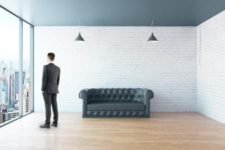 Geschäftsmann in der Loft-Zimmer mit schwarzen Ledersofa und Fenster im Boden