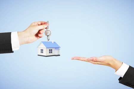 sold small: Mortgage concept with businessman handing house with key to another man on blue background Stock Photo