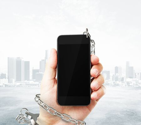 obsessed: Smartphone with blank screen cuffed to male hand on foggy city background. Concept of social problem. Mock up, 3D Rendering Stock Photo