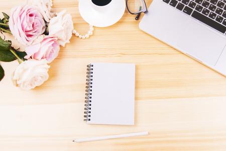 Draufsicht des Arbeitsplatzes der Frau mit unbelegter gewundener Notizblock, Blumen, Laptoptastatur und anderen Einzelteilen. Attrappe, Lehrmodell, Simulation Standard-Bild - 56566431