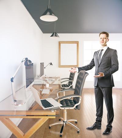 invitando: El hombre de negocios en el cargo con invitaci�n en blanco marco de imagen a tomar asiento en el escritorio con las computadoras y port�til. Maqueta, 3D