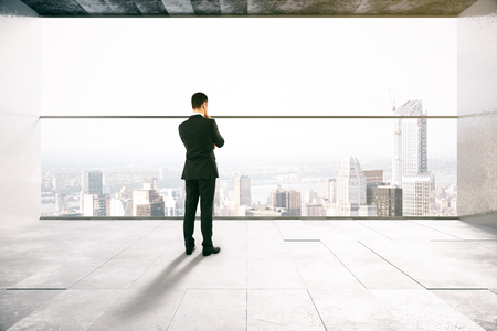 city view: Thoughtful businessman in concrete interior with city view. 3D Rendering