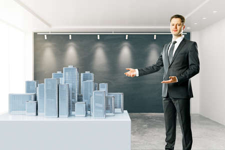 introducing: Businessman in interior standing next to city model with blackboard in the background. 3D Rendering