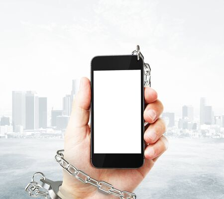 obsessed: Smartphone with blank white screen cuffed to male hand on foggy city background. Concept of social problem. Mock up, 3D Rendering