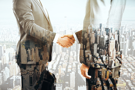 estate: Businesspeople shaking hands on city background. Double exposure