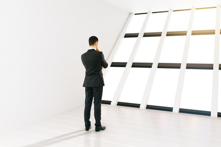 rearview: Thinking businessman in white room with panoramic windows. 3D Rendering Stock Photo