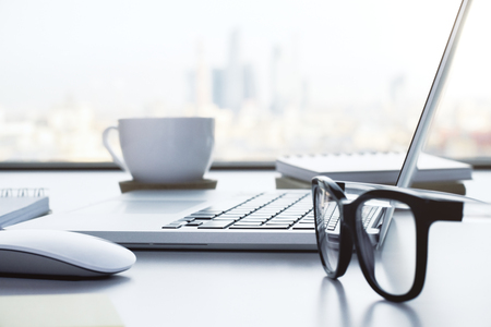 sulight: Closeup of white desktop with notebook, glasses, coffee cup, notepads and other items on blurry city background