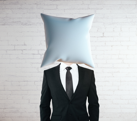 white headed: Pillow headed businessman on white brick wall background. Mock up Stock Photo