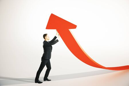 upholding: Success concept with businessman upholding red arrow on light grey background