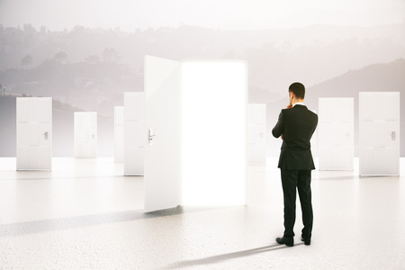 thoughtful: Success concept with thoughtful businessman looking at open door on abstract grey background. 3D Rendering
