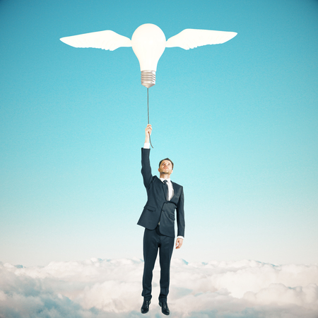 Idea concept with businessman holding lightbulb airballoon with wings on sky background Stock Photo