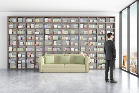 green couch: Thoughtful businessman in library interior with massive bookshelves, comfortable green couch and window with city view. 3D Rendering Stock Photo