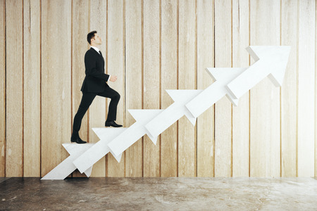 Success concept with businessman walking up abstract concrete arrow stairs on wooden plank background. 3D Rendering Фото со стока