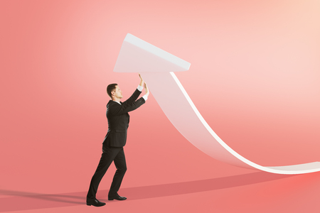 shadow man: Success concept with businessman upholding white arrow on light red background Stock Photo