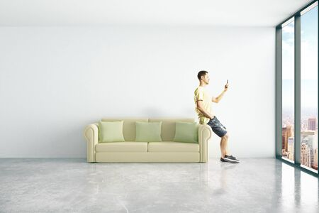 green couch: Young casual man sitting on green couch and using smart phone in concrete room with windows and city view. 3D Rendering