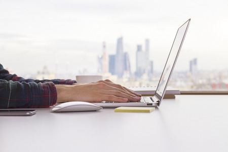 Female hands keyboarding on laptop placed on white desktop with computer mouse and smartphone with blurry city in the background