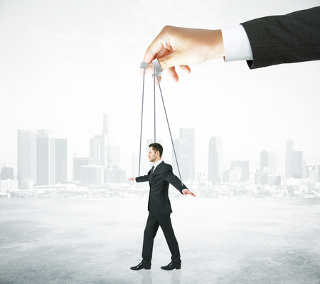 puppet master: Hand manipulating businessman puppet on ropes. Abstract city background. Concept of control Stock Photo