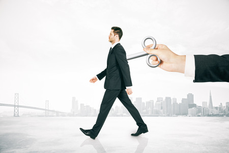 activating: Hand activating walking businessman with a wind-up key on his back on foggy city background. Concept of control Stock Photo