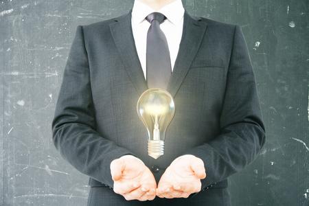 levitating: Idea concept with businessman holding levitating lightbulb on aged chalkboard background