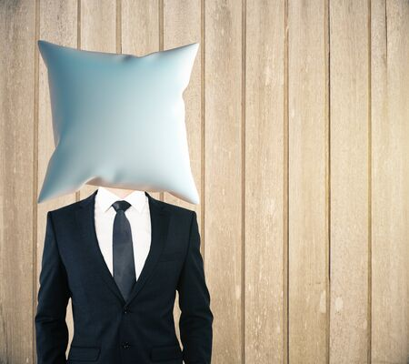 headed: Pillow headed businessman on wooden plank background. Mock up