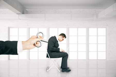 activating: Hand activating businessman with a wind-up key on his back in white brick room. Concept of control