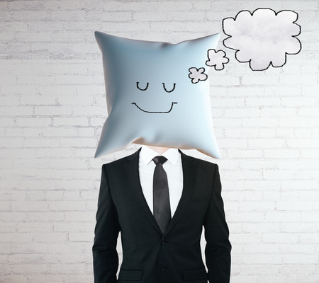 tired face: Sleeping businessman with smiley face on pillow instead of head dreaming about something with thought bubble on concrete background. Mock up