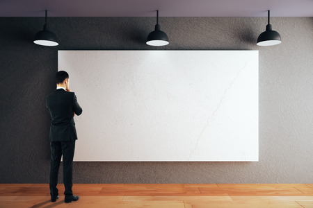 Thoughtful businessman looking at blank whiteboard on black concrete wall in room with wooden floor and ceiling with lamps. Mock up, 3D Rendering